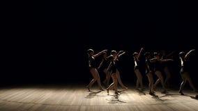 Μια ομάδα νέων κοριτσιών ballerina που χορεύουν στη σκηνή στο σκοτάδι, κινηματογράφηση σε πρώτο πλάνο φιλμ μικρού μήκους