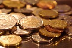 Μια ομάδα νομισμάτων που φωτογραφίζονται σε μια επιφάνεια καθρεφτών στοκ εικόνες με δικαίωμα ελεύθερης χρήσης