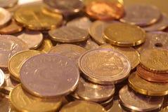 Μια ομάδα νομισμάτων που φωτογραφίζονται σε μια επιφάνεια καθρεφτών στοκ εικόνες