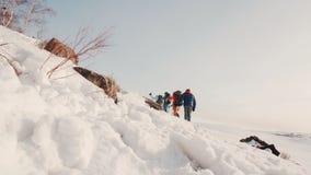 Μια ομάδα ορειβατών με την καλή προετοιμασία υπερνικά σίγουρα το βαθύ χιόνι στην κλίση ενός μικρού λόφου απόθεμα βίντεο