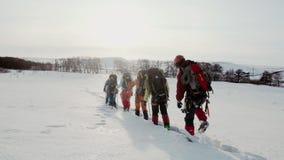 Μια ομάδα ορειβατών περνά με βεβαιότητα μέσω των βαθύτερων κλίσεων και κινείται σε μια γραμμή Πίσω από τους βαριά σακίδια πλάτης  απόθεμα βίντεο