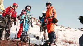 Μια ομάδα ορειβατών που στέκονται και που πίνουν το τσάι από ένα μπουκάλι thermos μιλούν, χαλαρώνουν και προετοιμάζονται να αναρρ φιλμ μικρού μήκους