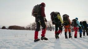 Μια ομάδα ορειβατών στα spiked παπούτσια, πηγαίνει αργά στη γραμμή στην επιφάνεια χιονιού, πίσω από τους, τα βαριά σακίδια πλάτης απόθεμα βίντεο