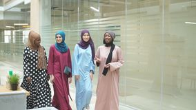 Μια ομάδα τεσσάρων νέων μουσουλμανικών multiethnic κοριτσιών που κουβεντιάζουν και που περπατούν μαζί στο επιχειρησιακό κέντρο φιλμ μικρού μήκους