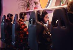 Μια ομάδα του επαγγελματικού cyber sportmans, τραίνα για το πρωτάθλημα, παίζει σε ένα τηλεοπτικό παιχνίδι multiplayer στο PC σε έ στοκ φωτογραφίες