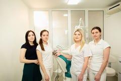Μια ομάδα των επαγγελματιών σε μια οδοντική κλινική, που θέτει κοντά στον εξοπλισμό στοκ εικόνες