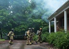 Μια ομάδα των πυροσβεστών παραβιάζει το σπίτι στοκ φωτογραφία με δικαίωμα ελεύθερης χρήσης