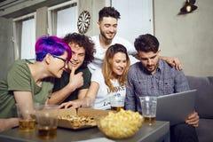 Μια ομάδα φίλων των σπουδαστών στον ελεύθερο χρόνο με ένα lap-top από κοινού Στοκ εικόνες με δικαίωμα ελεύθερης χρήσης