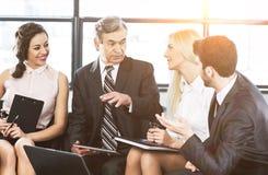 Μια ομάδα επιχειρηματιών που συζητούν την πολιτική επιχείρησης ` s σε ένα σύγχρονο γραφείο Στοκ Φωτογραφία