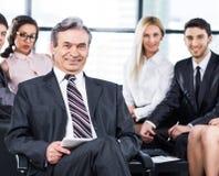 Μια ομάδα επιχειρηματιών που συζητούν την πολιτική η επιχείρηση στο γραφείο Στοκ Εικόνες