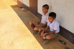 Μια ομάδα ευτυχών μη αναγνωρισμένων ταϊλανδικών παιδιών που κάθονται στο έδαφος με το χαμόγελο στα πρόσωπα Στοκ εικόνες με δικαίωμα ελεύθερης χρήσης