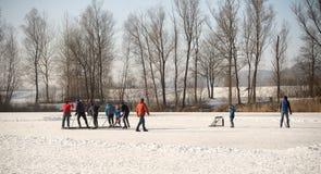 Μια ομάδα εφήβων καθαρίζει την επιφάνεια πάγου μιας παγωμένης λίμνης Στοκ εικόνες με δικαίωμα ελεύθερης χρήσης