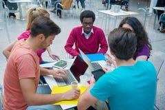Μια ομάδα εφήβων που κάθονται στον πίνακα στον καφέ, που χρησιμοποιούν το lap-top και που πίνουν το χυμό από πορτοκάλι Στοκ φωτογραφίες με δικαίωμα ελεύθερης χρήσης