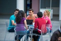 Μια ομάδα εφήβων που κάθονται στον πίνακα στον καφέ, που χρησιμοποιούν το lap-top και που πίνουν το χυμό από πορτοκάλι Στοκ εικόνα με δικαίωμα ελεύθερης χρήσης