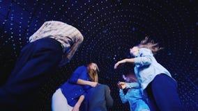 Μια ομάδα νέων που χορεύουν σε ένα νυχτερινό κέντρο διασκέδασης Χαμηλότερος ευρύς πυροβολισμός γωνίας φιλμ μικρού μήκους