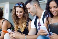 Μια ομάδα σπουδαστών που έχουν τη διασκέδαση με τα smartphones μετά από την κατηγορία Στοκ φωτογραφία με δικαίωμα ελεύθερης χρήσης