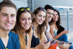 Μια ομάδα σπουδαστών που έχουν τη διασκέδαση με τα smartphones μετά από την κατηγορία Στοκ Εικόνες