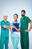 Μια ομάδα τριών νέων γιατρών Η ομάδα περιέλαβε έναν γιατρό και μια γυναίκα, δύο γιατροί ανδρών Είναι ντυμένοι σε πράσινο τρίβουν Στοκ φωτογραφίες με δικαίωμα ελεύθερης χρήσης