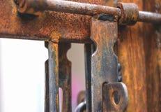 Μια οξυδωμένη πύλη με μια κλειδαριά λαβών στοκ εικόνα