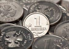 Μια πένα στο υπόβαθρο των νομισμάτων Στοκ Φωτογραφία