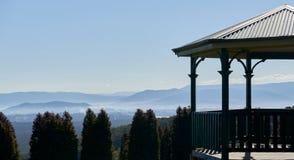 Μια πέργκολα υψηλή επάνω από μια κοιλάδα με την αμαρτία βουνών τα δέντρα απόστασης και πεύκων στο πρώτο πλάνο στοκ φωτογραφία με δικαίωμα ελεύθερης χρήσης