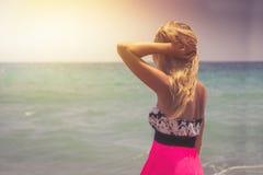 Μια πίσω πλάγια όψη σχετικά με μια θαυμάσια νέα προσοχή γυναικών στη θάλασσα και την αύξηση των χεριών της στην ανατολή στοκ φωτογραφία