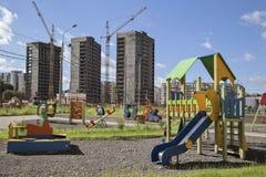 Μια παιδική χαρά ενάντια στα multi-storey κτήρια κάτω από την οικοδόμηση Στοκ Φωτογραφίες