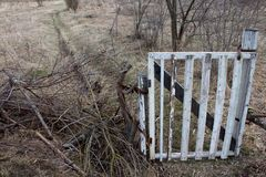 Μια παλαιά άσπρη πύλη κλείνει την είσοδο κατά μήκος μιας εθνικής οδού ρύπου, δύο διαδρομές στον τομέα στοκ εικόνες