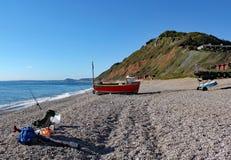 Μια παλαιά βάρκα στην παραλία σε Branscombe στο Devon, Αγγλία Στάσεις εξοπλισμού ψαράδων στο πρώτο πλάνο στοκ εικόνες