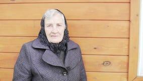 Μια παλαιά γιαγιά σε ένα μαύρο headscarf στέκεται σε ένα σπίτι απόθεμα βίντεο