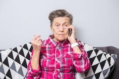 Μια παλαιά ηλικιωμένη γιαγιά γυναικών με την γκρίζα τρίχα κάθεται στο  στοκ φωτογραφία με δικαίωμα ελεύθερης χρήσης
