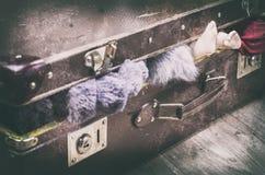 Μια παλαιά καφετιά βαλίτσα, κοντά, προεξέχοντα ενδύματα και πόδια μιας κούκλας στοκ εικόνα