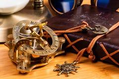 Μια παλαιά ναυτικά πυξίδα και ένα ηλιακό ρολόι ορείχαλκου στοκ εικόνες