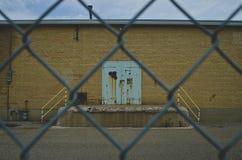Μια παλαιά σκουριά και ένα κιρκίρι χρωμάτισαν την πόρτα στον παλαιό τοίχο εργοστασίων μέσω του φράκτη στοκ φωτογραφία