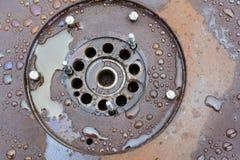 Μια παλαιά, σκουριασμένη, υγρή ρόδα που καλύπτεται με τις φρέσκες σταγόνες βροχής υπαίθρια Σκουριά σε μια επιφάνεια μετάλλων r r στοκ φωτογραφία με δικαίωμα ελεύθερης χρήσης