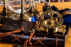 Μια παλαιό ναυτικό πυξίδα και ένα ηλιακό ρολόι ορείχαλκου, με ένα περιοδικό δέρματος, προστατευτικά δίοπτρα και μια κλεψύδρα ορεί στοκ εικόνες