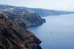 Μια πανοραμική άποψη της λευκιάς πόλης με τις μπλε στέγες στα πλαίσια του Αιγαίου πελάγους - το πιό ρομαντικό νησί Santorini στοκ εικόνα