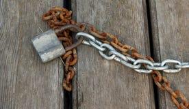 Μια παλαιά σκουριασμένη αλυσίδα σιδήρου και μια νέα αλυσίδα αργιλίου με ένα παλαιό σκουριασμένο λουκέτο στις ξύλινες επιτροπές Στοκ Εικόνα