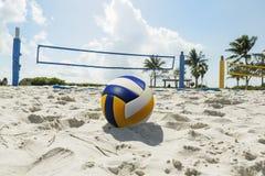 Μια πετοσφαίριση παραλιών καθαρή σε μια ηλιόλουστη παραλία, με τους φοίνικες Στοκ φωτογραφία με δικαίωμα ελεύθερης χρήσης