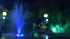 Μια πηγή με το χρωματισμένο φωτισμό νερού, το βράδυ κινηματογράφηση σε πρώτο πλάνο, θαμπάδα, 4k απόθεμα βίντεο