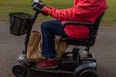 Μια πλευρά στον πυροβολισμό μιας ηλικιωμένης κυρίας σε ένα κόκκινο παλτό που απολαμβάνει της ελευθερίας ενός ηλεκτρικού μηχανικού στοκ εικόνες