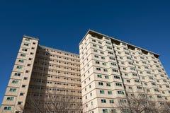 Μια πολυκατοικία των συμβουλίων ενάντια σε έναν σαφή μπλε ουρανό Κατειλημμένος κυρίως από τους παραλήπτες ευημερίας, τους μετανάσ στοκ εικόνα