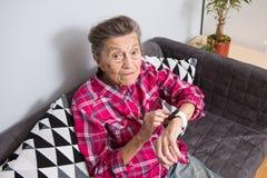 Μια πολύ παλαιά ανώτερη καυκάσια γιαγιά με την γκρίζα τρίχα και τις βαθιές ρυτίδες κάθεται στο σπίτι στον καναπέ στα τζιν και ένα στοκ φωτογραφίες με δικαίωμα ελεύθερης χρήσης