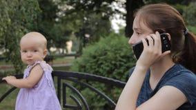 Μια πολύ νέα παραμάνα που απαντά στο smartphone και που μιλά ενώ το μωρό στέκεται δίπλα στην εκμετάλλευσή της από την πλάτη πάγκω φιλμ μικρού μήκους