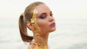 Μια προκλητική γυναίκα με το επαγγελματικό χρυσό makeup εξετάζει τη κάμερα και φλερτάρει με το θεατή Δαγκώνει το χείλι και τις στ απόθεμα βίντεο