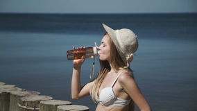 Μια προκλητική νέα γυναίκα σε ένα θερινό καπέλο και ένα άσπρο μαγιό μπικινιών, που παίρνουν τα λουτρά ήλιων, πίνει το νερό από έν φιλμ μικρού μήκους