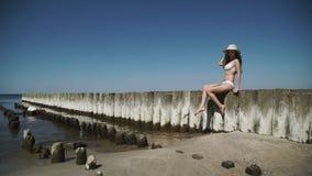 Μια προκλητική νέα γυναίκα σε ένα θερινό καπέλο και ένα λευκό μαγιό μπικινιών, που παίρνει τα λουτρά ήλιων, σε μια αμμώδη παραλία φιλμ μικρού μήκους