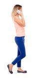 Μια πλάγια όψη μιας γυναίκας που περπατά με ένα κινητό τηλέφωνο Στοκ Εικόνες