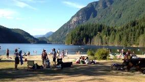 Μια πλευρά των ανθρώπων που έχουν τη διασκέδαση σε μια ειρηνική ακτή λιμνών φιλμ μικρού μήκους