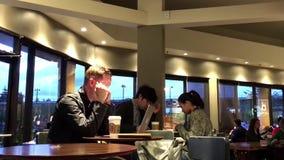 Μια πλευρά των ανθρώπων που πίνουν τον καφέ και που μιλούν στο φίλο με το κινητό τηλέφωνο φιλμ μικρού μήκους